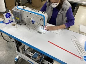 A person wearing a protective face mask sits while sewing face masks at Culp Inc.